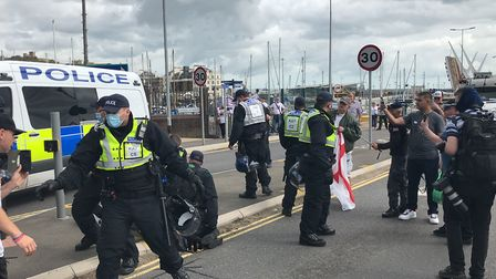 Police restrain protesters on the ground by the entrance to Dover harbour, who are demonstrating aga