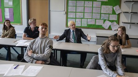 Prime Minister Boris Johnson with year 11 pupils as he tours Castle Rock school, Coalville, in the e
