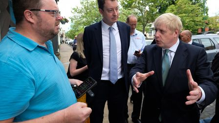 Conservative party leader Boris Johnson and Simon Clarke MP speak to a steelworker during a visit to