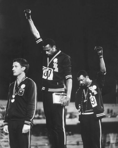 American track and field athletes Tommie Smith (C) and John Carlos (R), protest with the Black Power
