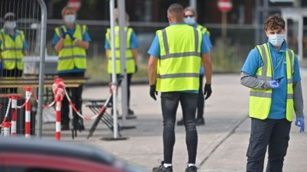 Workers wear NHS Test and Trace branded Hi-Vis jackets as they work at a COVID-19 testing centre