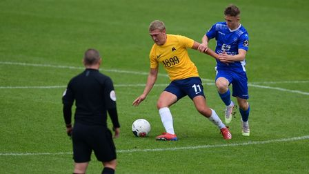 Jake Andrews of Torquay United holds off Dan Warre of Chippenham Town during the pre-season friendly at Plainmoor.