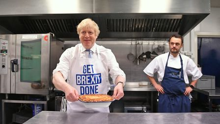 Prime Minister Boris Johnson holds a freshly baked pie while wearing a 'get Brexit done' apron